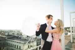 Slut upp ståenden av lyckligt le förälskat posera för par på taket med stora bollar E Arkivbild