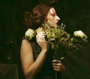 Slut upp ståenderedhairkvinna med torra blommor för ljust idérikt sminkinnehav arkivbilder