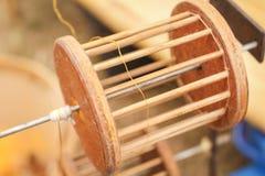 Slut upp träutrustning som reeling tråden från guld- silkesmaskkokonger i kruka på kolugnen för att göra den siden- tråden, siden royaltyfri bild