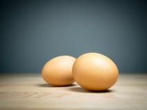 Slut upp två ägg på trätabellen Arkivfoto