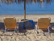 Slut upp två gula tomma sunbeds med solparaplyet på den grekiska sandiga stranden med vatten för hav för turkosfrikändblått arkivbilder