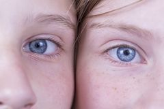 Slut upp två ung flickaögon, parståendebarn, makro, inomhus Royaltyfri Bild