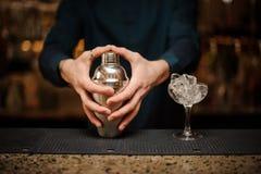 Slut upp unga barmanshänder med shaker arkivbilder