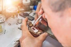 Slut upp urmakaren som reparerar den gamla klockan för mekanism royaltyfri foto