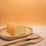 Slut upp vaniljkakarulle i trämaträtt på trätabell- och apelsinbakgrund med kopieringsutrymme Royaltyfria Bilder