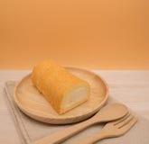 Slut upp vaniljkakarulle i trämaträtt på trätabell- och apelsinbakgrund med kopieringsutrymme Arkivbilder
