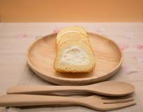 Slut upp vaniljkakarulle i trämaträtt på trätabell- och apelsinbakgrund med kopieringsutrymme Arkivbild