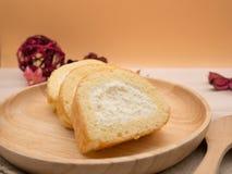 Slut upp vaniljkakarulle i trämaträtt på trätabell- och apelsinbakgrund med kopieringsutrymme Arkivfoton