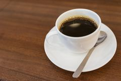 Slut upp varm espresso med bubblor i kopp för vitt kaffe på trätabellen nära fönster i coffee shop i morgonen i mjuk tappning royaltyfria foton
