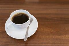 Slut upp varm espresso med bubblor i kopp för vitt kaffe på trätabellen nära fönster i coffee shop i morgonen i mjuk tappning royaltyfria bilder