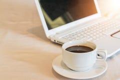 Slut upp varmt svart kaffe i den vita koppen med den vita bärbara datorn arkivbild