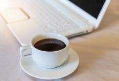 Slut upp varmt svart kaffe i den vita koppen med vit bärbar datorbakgrund fotografering för bildbyråer