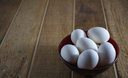 Slut upp vita fega ägg, inom en bunke, på en trätabell royaltyfri foto