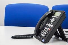 Slut upp voipIP-telefonen på tabellen i styrelsen för ledningmöte royaltyfri foto