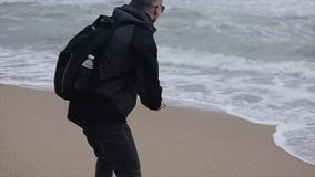 Slutbaksidasikt av en man som upp väljer en sten på stranden och kastar den in i havet arkivfilmer