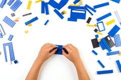 Slutet av barn` s räcker upp att spela med färgrika plast- tegelstenar på tabellen arkivfoton