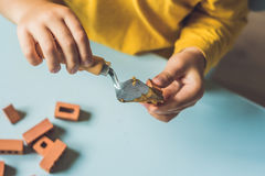 Slutet av barn` s räcker upp att spela med verkliga små lerategelstenar på tabellen Litet barn som har gyckel och bygger ut ur ve Royaltyfria Bilder