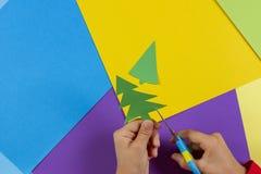 Slutet av barn` s räcker upp den bitande julgranen från kulört papper för att förbereda handgjorda garneringar eller kortet för n royaltyfri bild