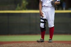 Slutet av basebollspelare lägger benen på ryggen upp med röda strumpor som står på arkivbild