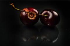 Slutet av bilden av ruttna röda körsbär bär frukt upp på reflekterande bla Fotografering för Bildbyråer