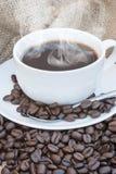 Slutet av coffe kuper upp och sauceren som omges av bönor på hessian arkivfoton