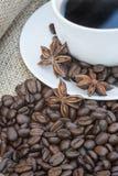 Slutet av coffe kuper upp och sauceren som omges av bönor på hessian arkivfoto