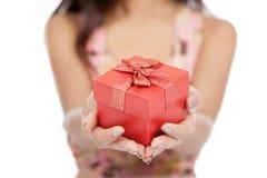Slutet av den asiatiska kvinnan ger upp den röda fokusen för gåvaasken på gåvan Arkivbild