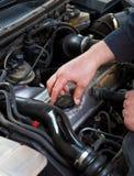 Slutet av den auto mekanikern öppnar upp det olje- locket Arkivbild