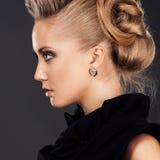 Slutet av den blonda kvinnan med danar upp frisyren Royaltyfri Bild