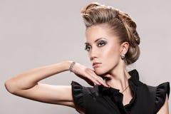 Slutet av den blonda kvinnan med danar upp frisyren Fotografering för Bildbyråer