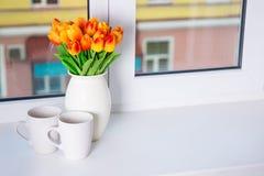 Slutet av den härliga apelsinen blommar upp i vas och två koppar på en w Royaltyfri Bild