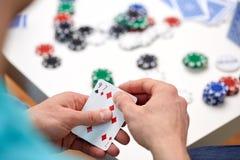 Slutet av den manliga handen med att spela cards och gå i flisor upp Arkivfoto