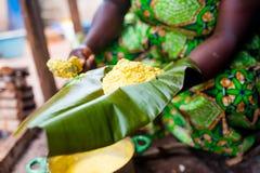 Slutet av den traditionella afrikanska havrefoufouen på pisangbladet rymde upp vid kvinnan i traditionell klänningmatlagning arkivbild