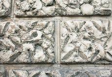 Slutet av en buse texturerade upp murbrukväggbeläggningen, efterföljd av stenmurverket Abstrakt grå patchy bakgrund Arkivbild