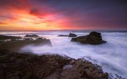Slutet av en färgrik dag på en isolerad strand som beskådar solnedgången arkivbild