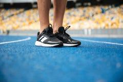 Slutet av en man lägger benen på ryggen upp, i att stå för gymnastikskor Fotografering för Bildbyråer