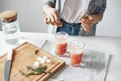 Slutet av flicka` s räcker upp att dekorera grapefruktdetoxen den sunda smoothien med rosmarin Royaltyfri Foto
