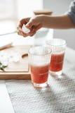 Slutet av flicka` s räcker upp att sätta isstycken i exponeringsglas med den sunda smoothien för grapefruktdetoxen Royaltyfri Fotografi