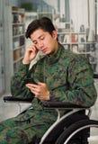Slutet av fundersamt barn tjäna som soldat upp sammanträde på hjulstol som använder hans mobiltelefon, i en suddig bakgrund Royaltyfri Bild