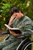 Slutet av fundersamt barn tjäna som soldat upp sammanträde på hjulstol som läser en bok i uteplatsen, i en trädgårdbakgrund Arkivfoto