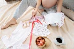 Slutet av gravida kvinnan som poserar med gulligt, behandla som ett barn upp kläder Royaltyfria Bilder
