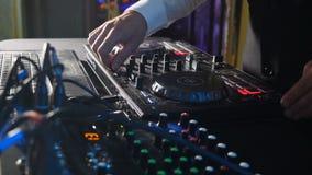 Slutet av h?nder av discjockeyn spelar upp musik som blandar och skrapar p? skivtallrikmusikutrustning Yrkesm?ssig musikutrustnin arkivfilmer
