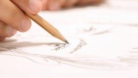 Slutet av handen med blyertspennateckningen skissar upp på papper Royaltyfri Foto