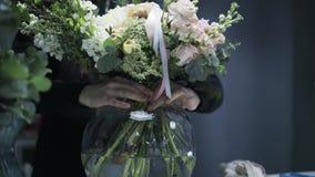 Slutet av kvinna s räcker upp att sätta en härlig grupp av blommor i en vas stock video