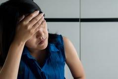 Slutet av kvinnafördjupningen har upp en huvudvärk och en känslig sorgsenhet i sovrum royaltyfria foton