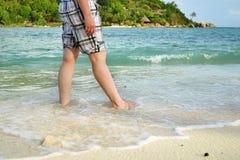 Slutet av kvinnan lägger benen på ryggen upp att gå barfota på sanden i sommar ho arkivfoto