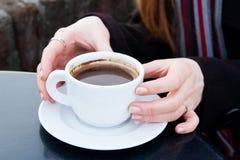 Slutet av kvinnan räcker upp att rymma en coffekopp i en caffe Royaltyfria Bilder