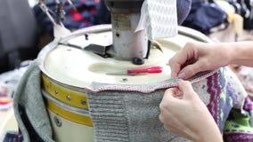 Slutet av kvinnan räcker upp att sy en overlock på symaskinen arkivfilmer