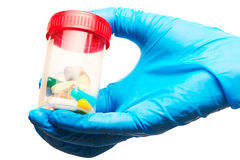 Slutet av kvinnliga doktorns hand i den blått steriliserade kirurgiska handsken som rymmer den genomskinliga plast- sterila provs Fotografering för Bildbyråer