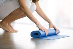 Slutet av kvinnlign räcker upp att rulla ut matt yoga Arkivbild